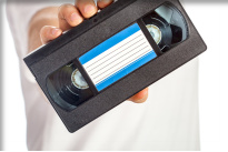 Video tape cassete (VHS) with blue label hold by male hand